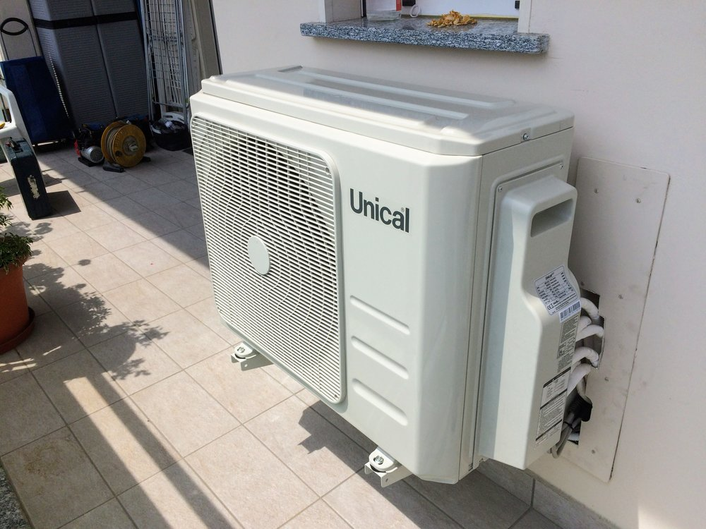 Unità esterna staffata a parete con scarico di condensa per l'utilizzo in pompa di calore in inverno.
