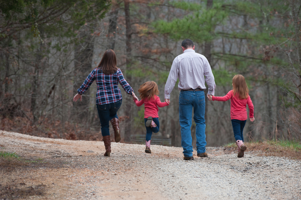 family of four walking down a dirt road holding hands