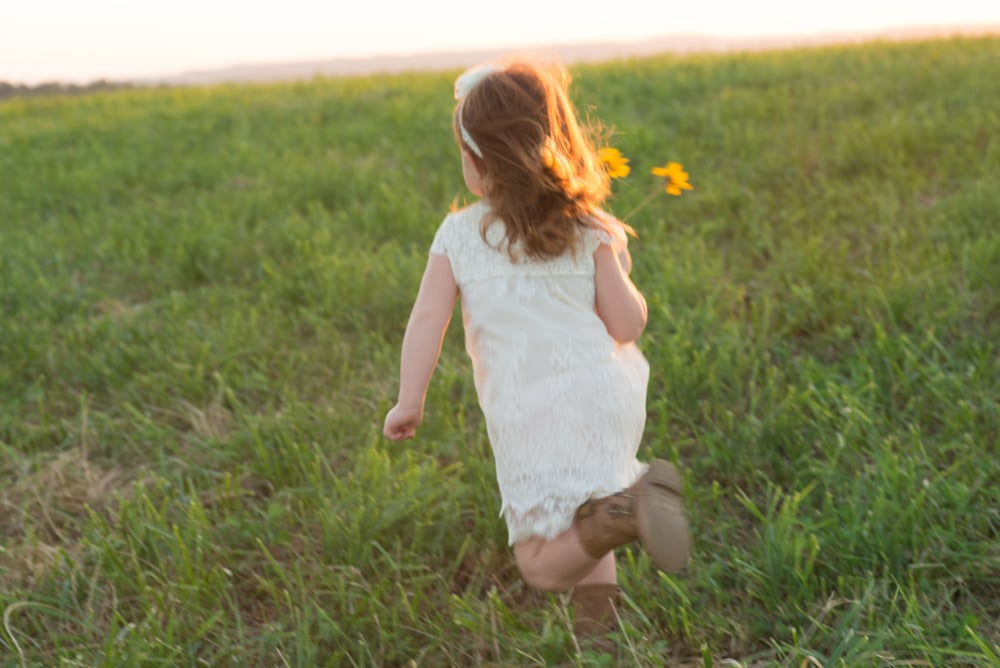 little girl running with a flower in a meadow at sunset