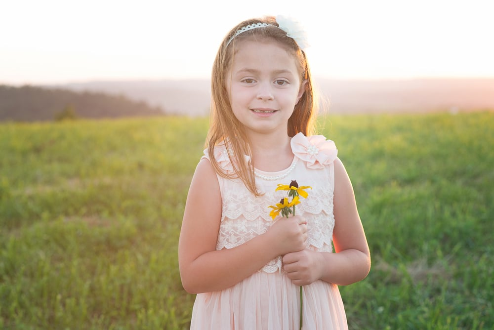 little girl holds a flower at sunset
