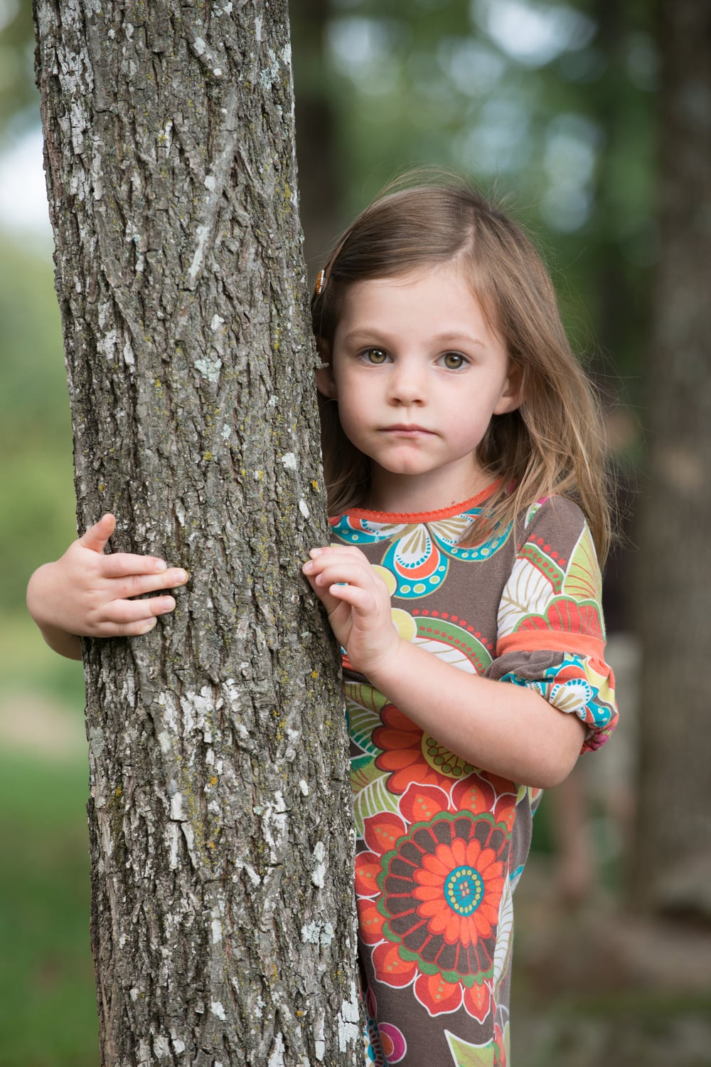 Little girl hiding behind tree