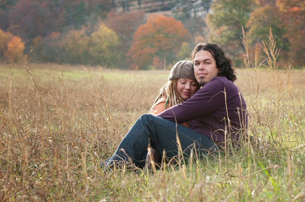 Engaged couple sitting in a meadow at sunset