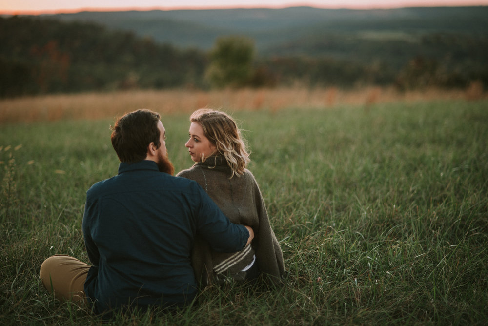 Couple sits in a meadow at sunset