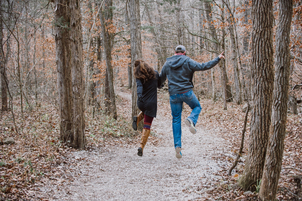 Couple skipping down a wooded trail