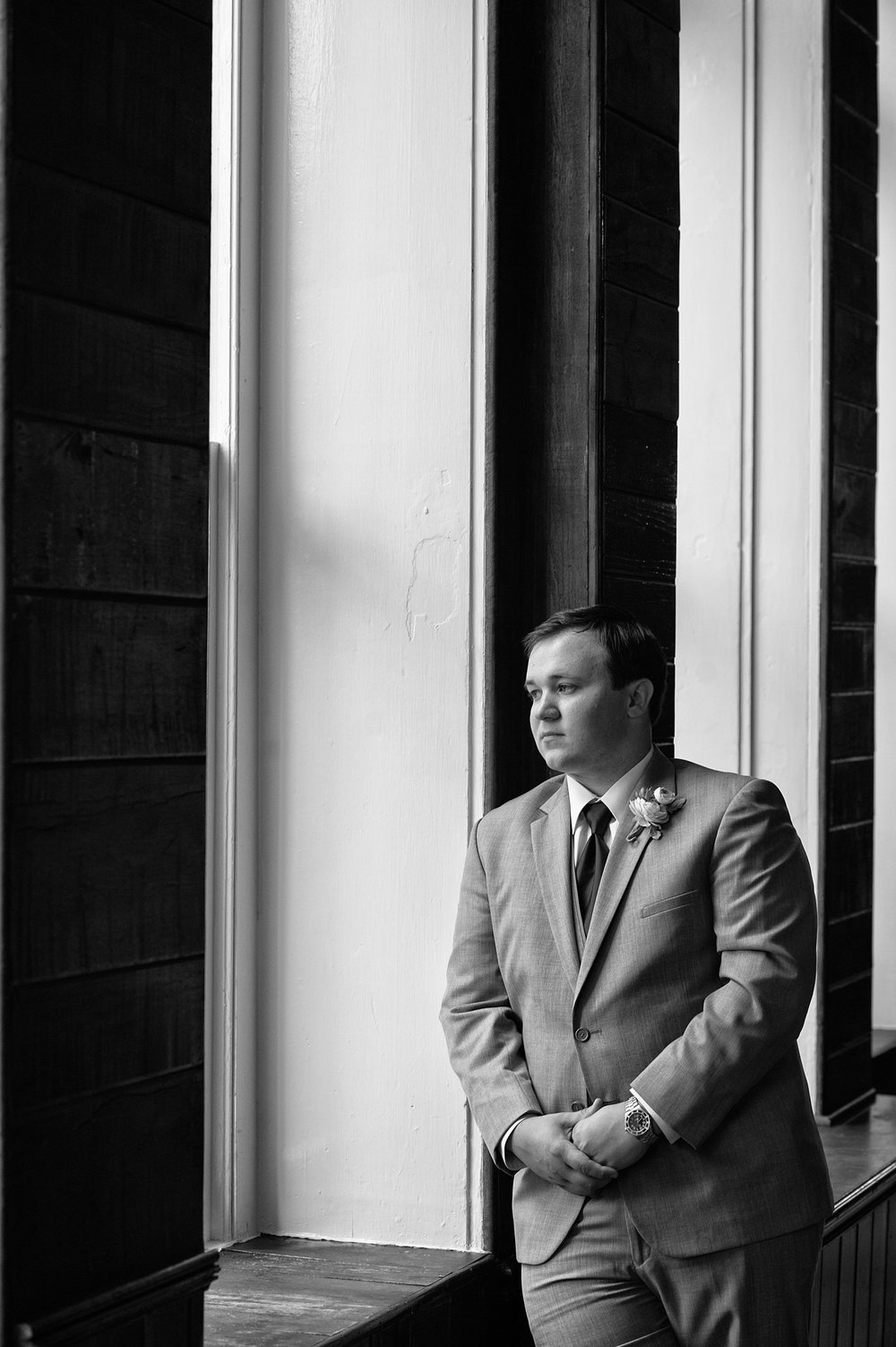 Groom looking out window, black and white image