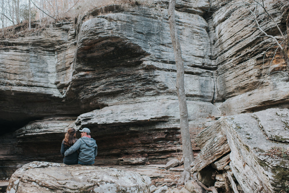 Engagement couple sits among boulders in Lost Valley