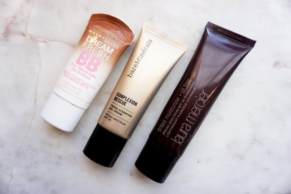"From Left to Right:  Maybelline Dream Fresh BB Cream in ""Deep Sheer Tint""  BareMinerals Complexion Rescue Tinted Hydrating Gel Cream in ""Chestnut 09""  Laura Mercier Tinted Moisturizer in ""Mocha"""