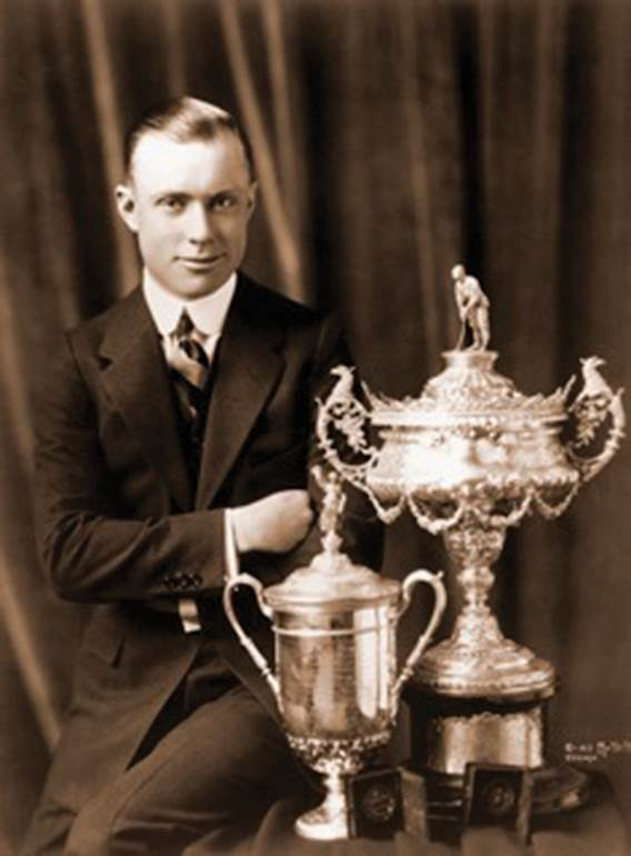 Chick Evans with the U.S. Open and Amateur trophies.