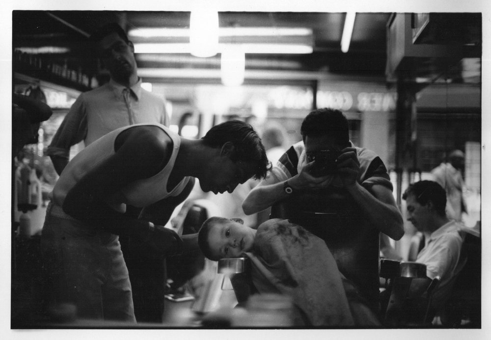 Tyrone having his hair cut in the shop as a kid, photographed by Kadir Guirey.