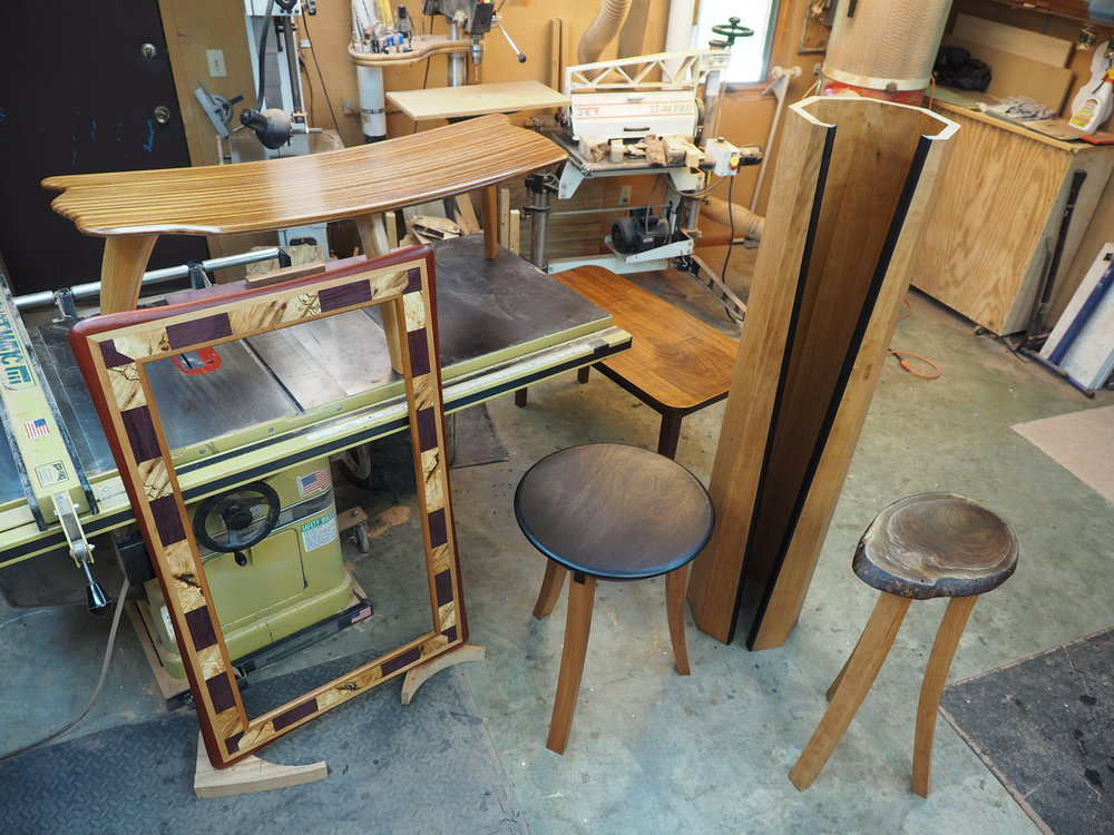 L to R: A Bayfield Collection Burl Mirror, Bent Lamination Coffee table (on the saw), 3-leg Showcase Table, Open Portal Lamp, and a small Showcase Table (live edge top).