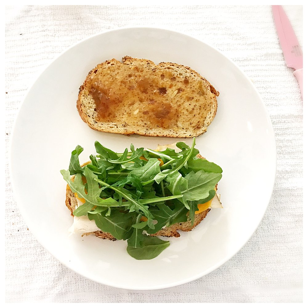 8.  Remove sandwich half from the oven.    9.  Place heated sandwich half on your serving plate & top with the fresh arugula.    10.  Top arugula with the second slice of bread spread with the fig preserves.
