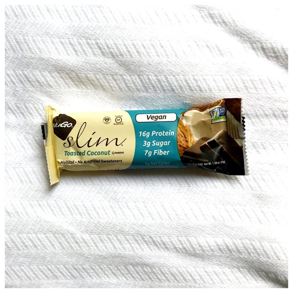 "NuGo Slim    Nutrition Info   This is one ""protein bar"" I have found that (1) actually contains a substantial amount of protein (2) while not being super high in calories, (3) is not packed with sugar OR artificial sweeteners, and (4) tastes good!  These bars have about  17 grams of protein  per bar, about  170 or 180 calories , and about  3 grams of sugar .     Workout Fuel   With so much protein, this would not be the best pre-exercise, especially high intensity exercise, snack.  It could make a good post-exercise snack, specifically after resistance training exercise, or a good part of a breakfast or lunch, when a boost in protein is needed.   Food Allergy Friendly   I recently saw a client who was just diagnosed with several food allergies.  When I went to the Nu Go Nutrition page to check out all of their products, I found that they make bars to accommodate all types of allergies or dietary needs (dairy-free, gluten-free, nut-free, vegan, etc.).  Each bar may vary, so take a close look at the ingredient label."