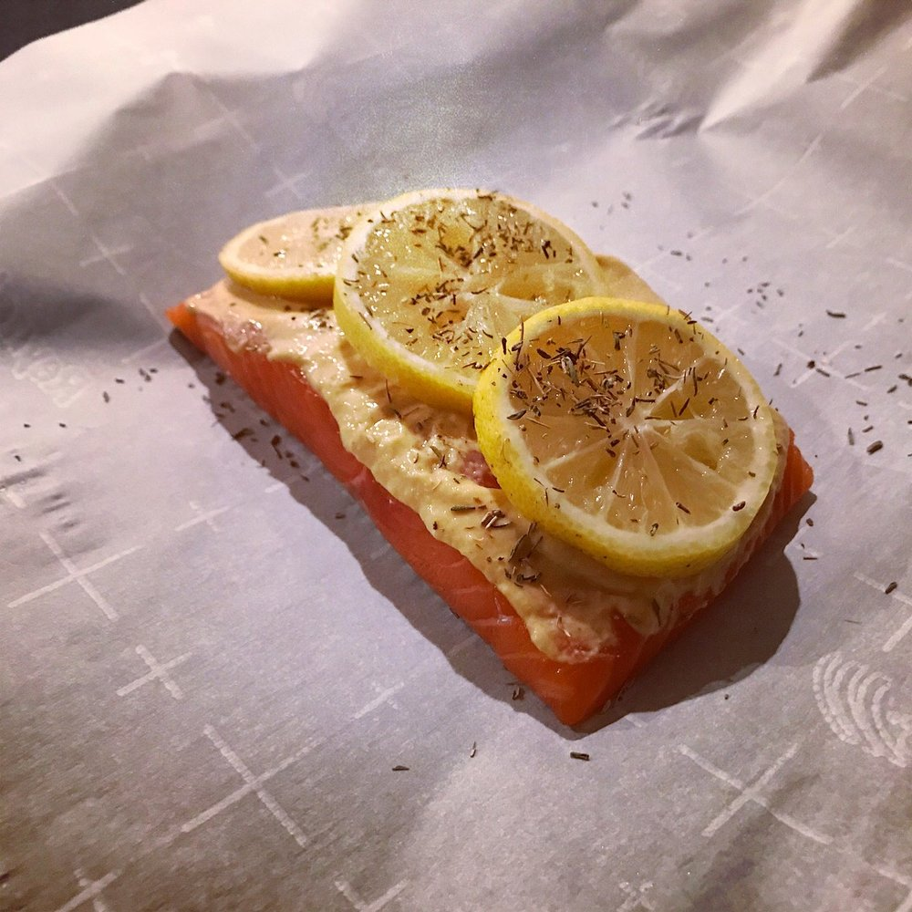 4. Lay salmon filet on parchment paper.  5. Spread Dijon mustard in an even layer over the salmon filet.  6. Lay the 3 lemon slices over the Dijon.  7. Sprinkle the dried thyme over the lemon slices and salmon - or lay thyme sprigs on top if using.