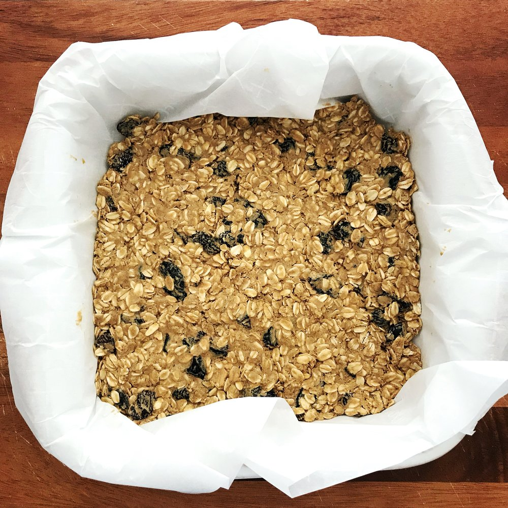 3.  Line a 9x9 inch baking dish with parchment paper.  4.  Spread oat - Sun Butter mix out evenly along bottom of dish, making sure to get to all sides and corners.