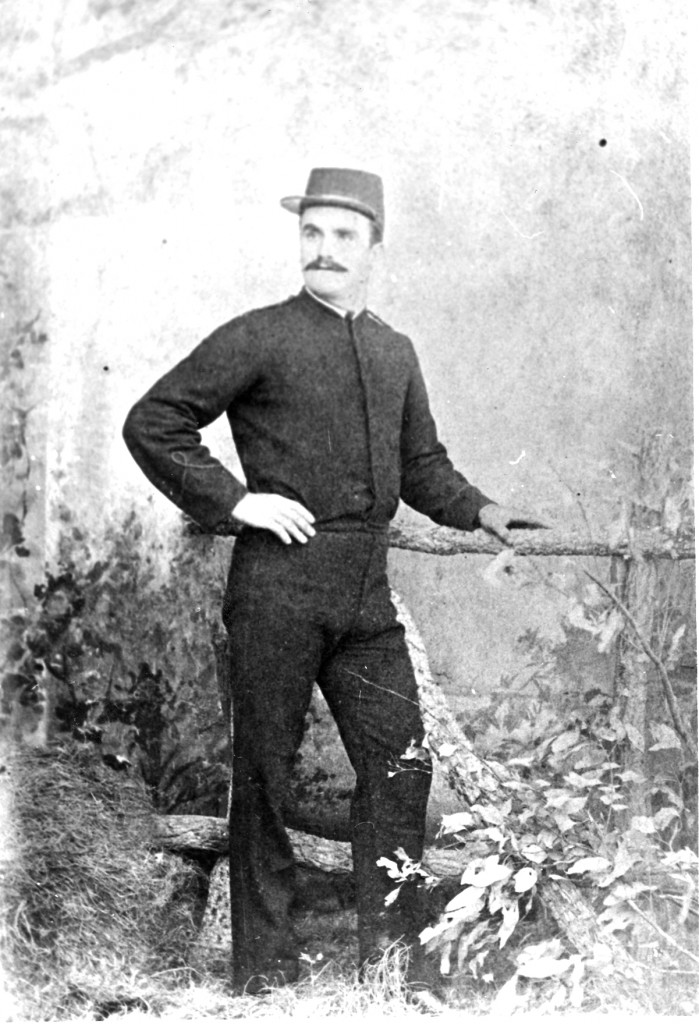 Full length studio portrait of police officer wearing the first Queensland Police uniform of dark blue, serge wool. This uniform came into being in 1864 and was still in use well into the 20th century in the more populated areas. Note that there are no identifying badges or patches to signify an association with the police. The first hat badges showing the words Queensland Police, were not introduced until 1884. (QP Museum)