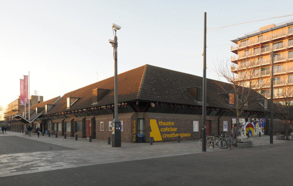 Image shows the entrance of the Albany. It is a brown, one story brick building with yellow lettering.Source: Vocal Eyes