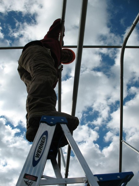 Balancing the (very tall) ladder for the (very precariously perched) farmer!