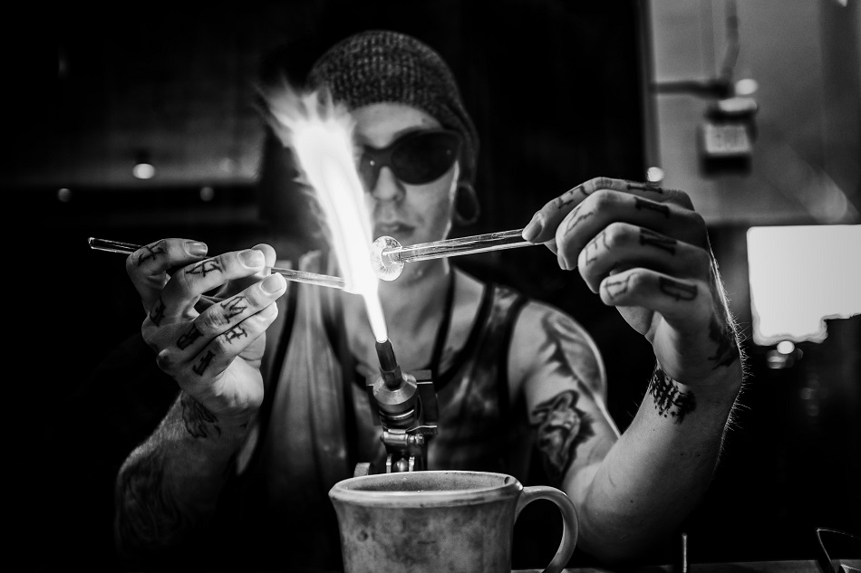 Glass artist with flame and tattoos
