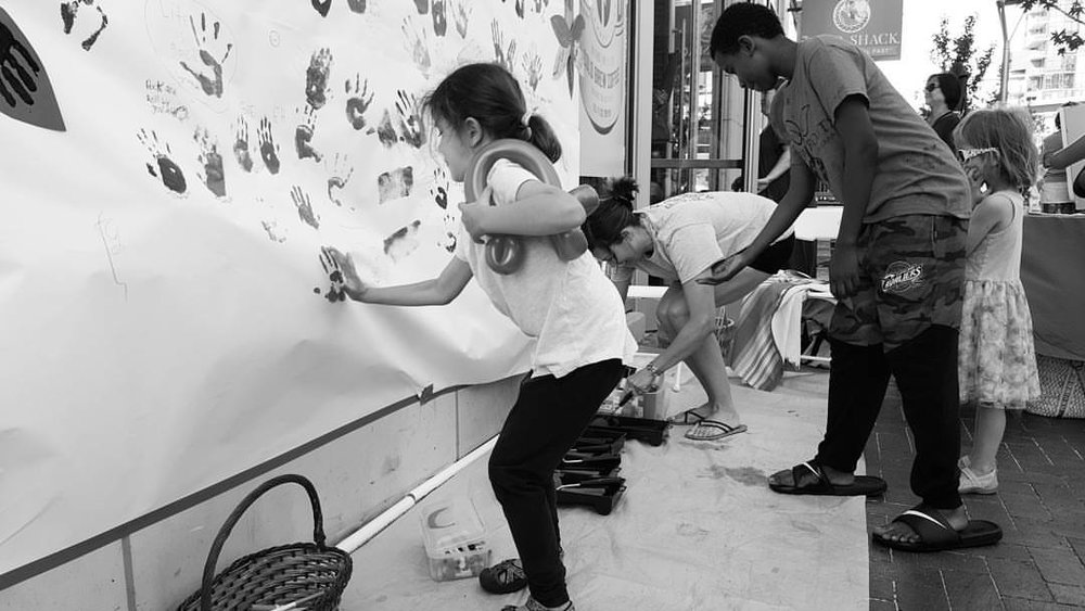 Putting Hand Prints on Paper, World Refugee Day - Boise, Idaho