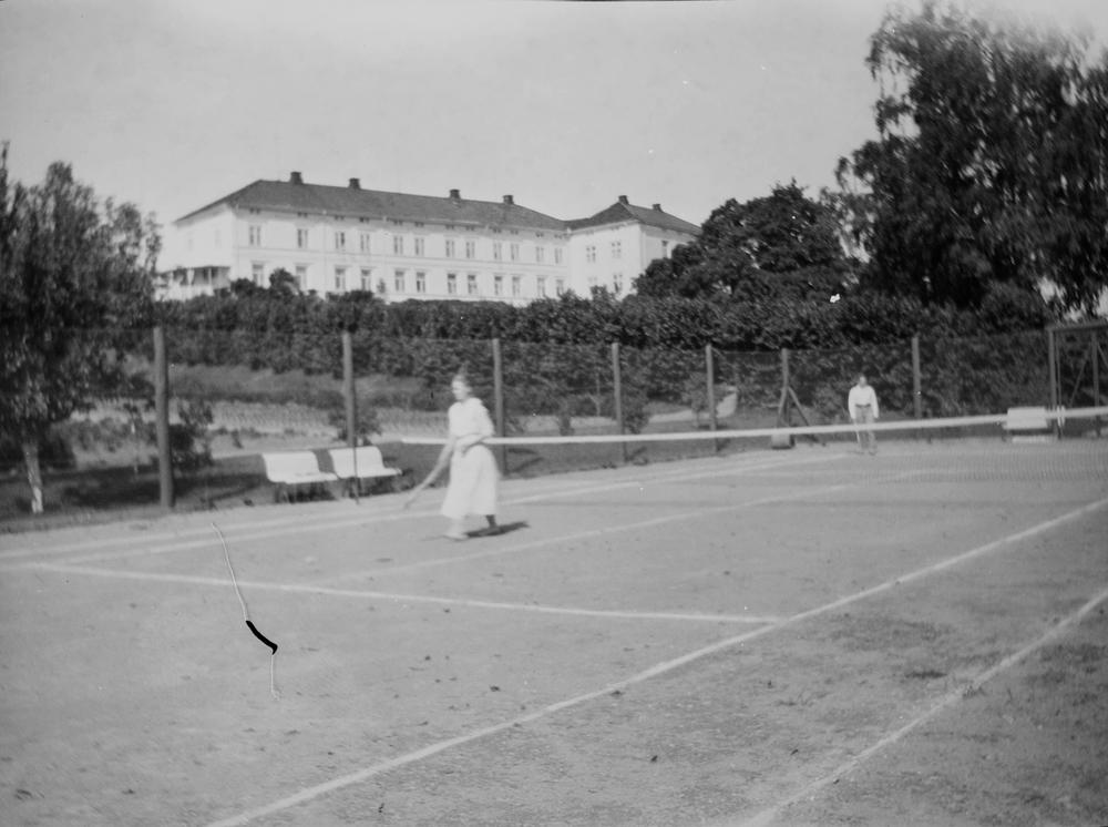 Tennis i hagen på Linderud Gård, datert sommeren 1922(datering av konvolutt fra fotograf 15/8-22).I bakgrunnen synes hovedhuset og hasseltunnelen.