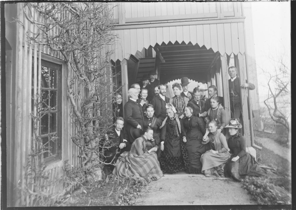 Gruppebilde, ca. 1890.Familien er samlet under et tidligere til- og overbygg på baksiden av hovedhuset på Linderud Gård.