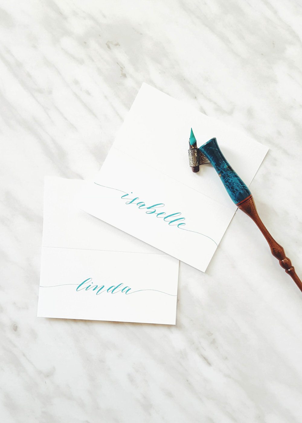 Hand written place cards in turquoise gouache