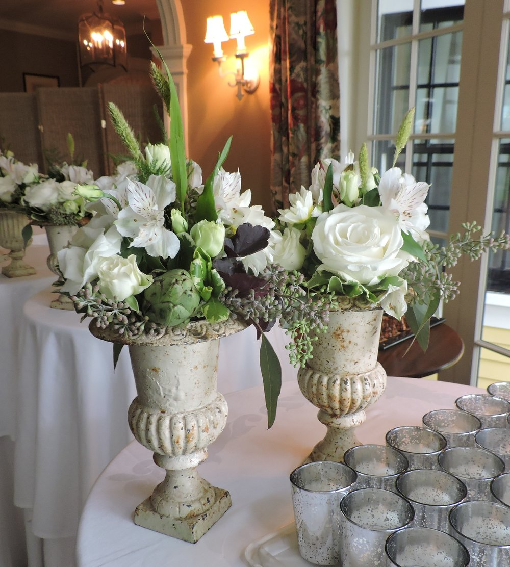 Wrought iron urns with artichokes, seeded eucalyptus, roses and other flowers are lined up for the cocktail hour. The Country Club, Brookline, MA