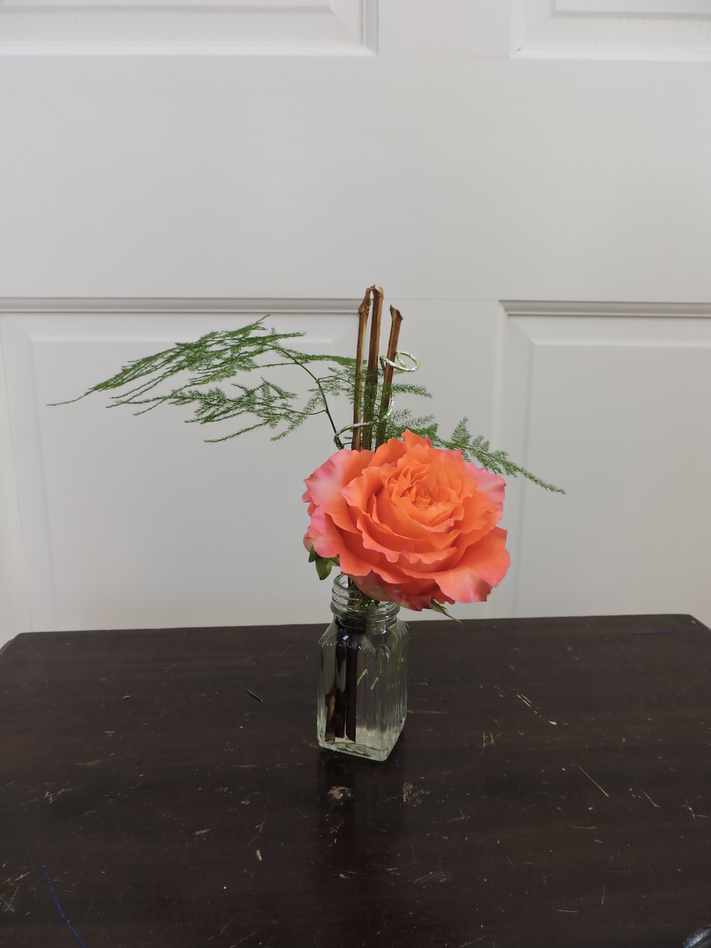 A beautiful rose, plumosa fern and twigs wrapped with decorative wire. Shaker Hills County Club
