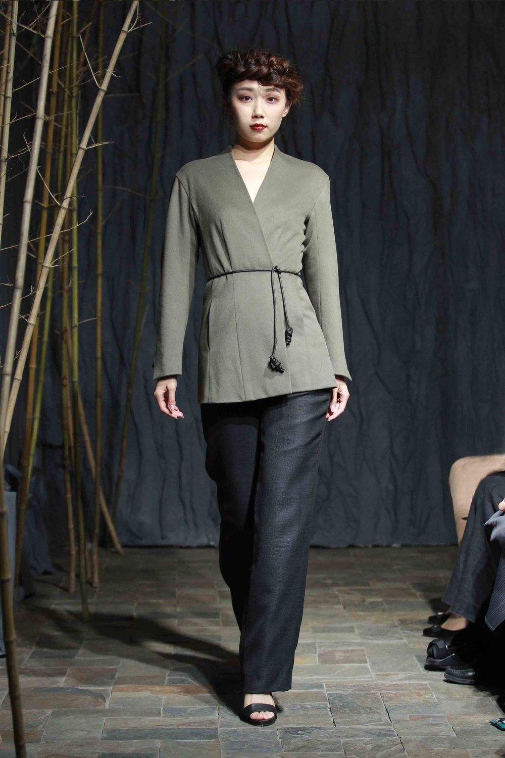 Moss-green clean-cut long jacket with delicate brooch// anthracite straight-cut pants