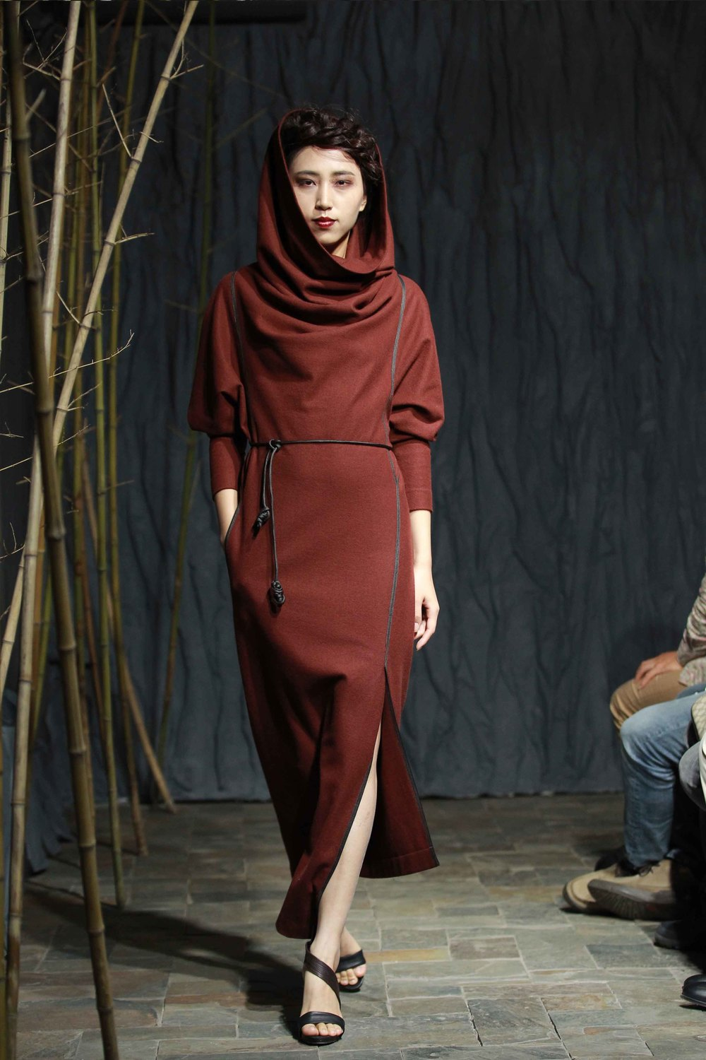 Rust-red spiral-cut wool dress with generous triangular batwing sleeves