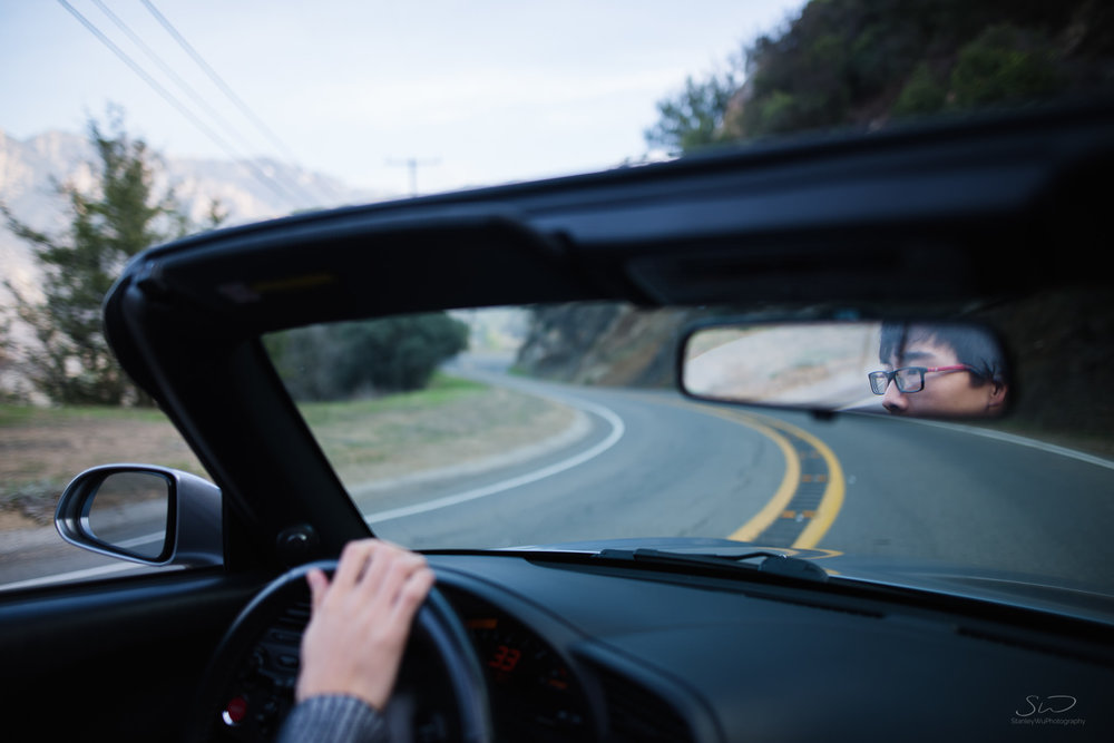 creative portrait of sports car s2000 driver with face in mirror juxtaposed with a curvy road that he's focusing on