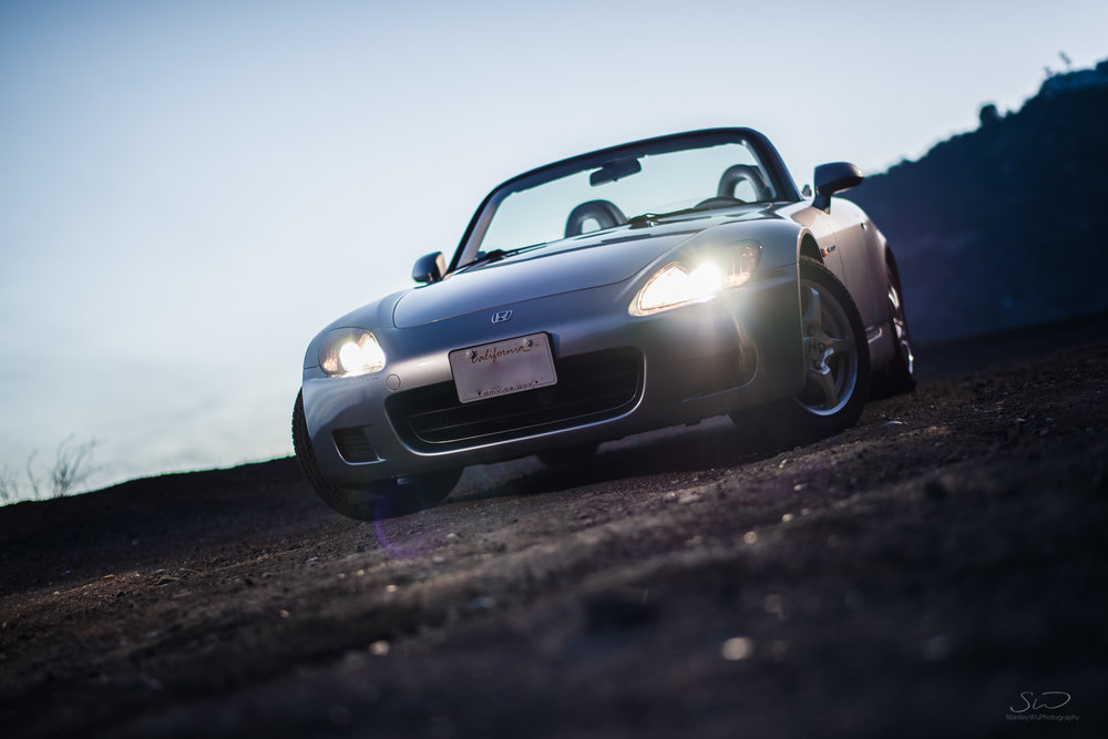 edgy blue twilight shot of honda s2000 with high beams on in malibu california
