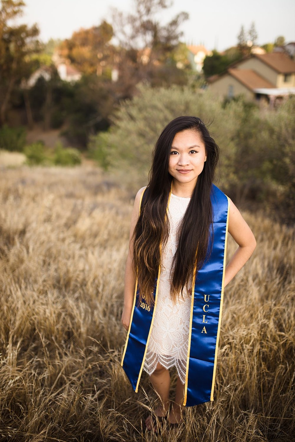beautiful graduation senior portrait of a girl standing among wheat colored grass in san fernando valley in los angeles