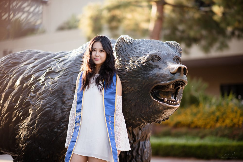 beautiful graduation senior portrait of a girl standing in front of the bruin bear at ucla in los angeles