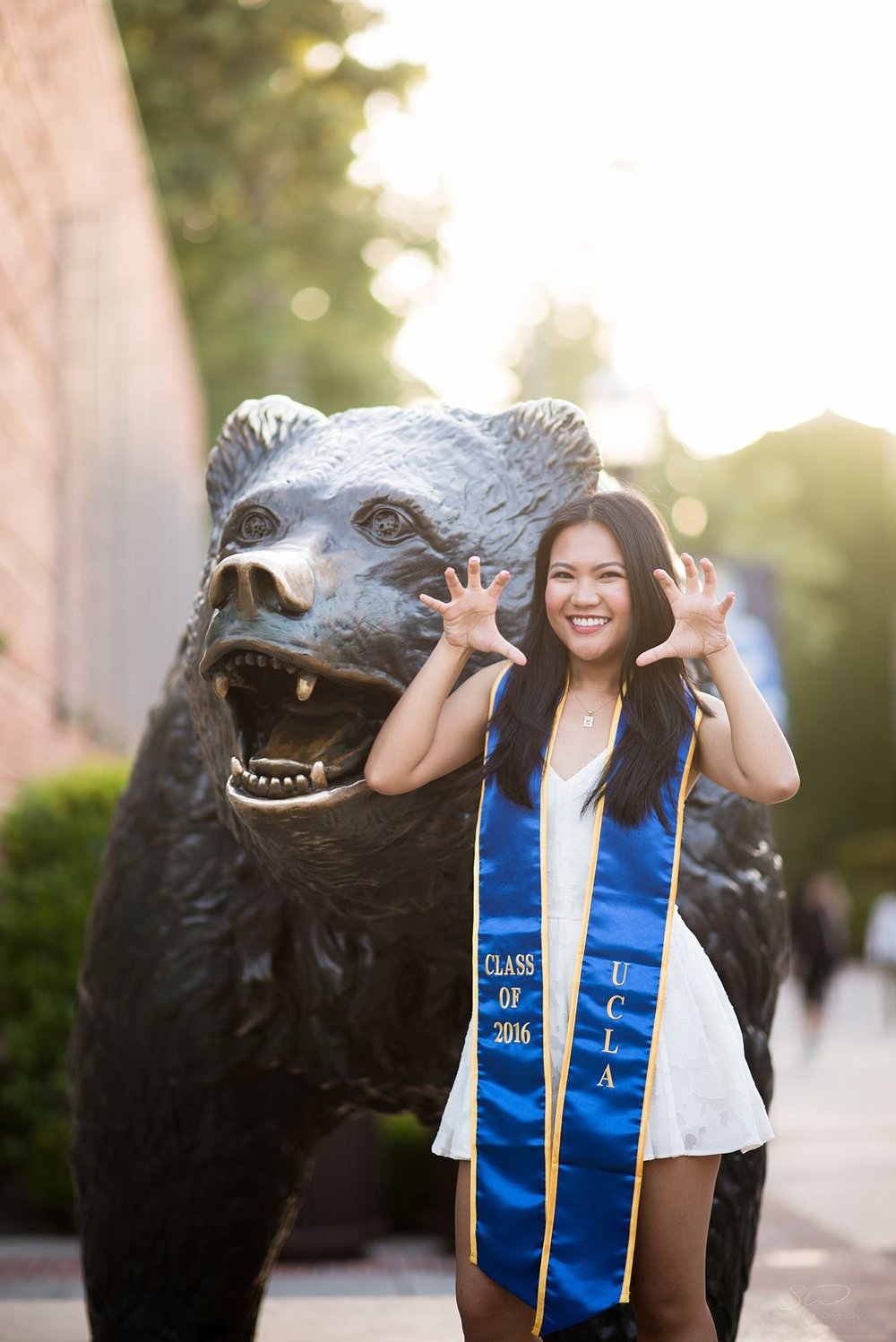 cute graduation senior portrait of a girl pretending to be a bear in front of the bruin bear at ucla in los angeles