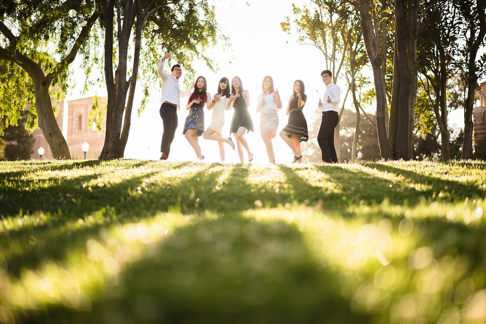 epic graduation senior portrait of a group having fun with their epic shadows streaming through onto grass at ucla in los angeles