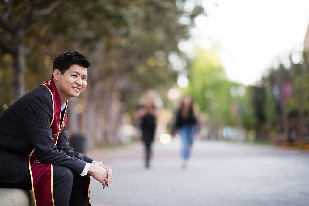graduation senior portrait of a man sitting in front of a blurred out street at usc in los angeles