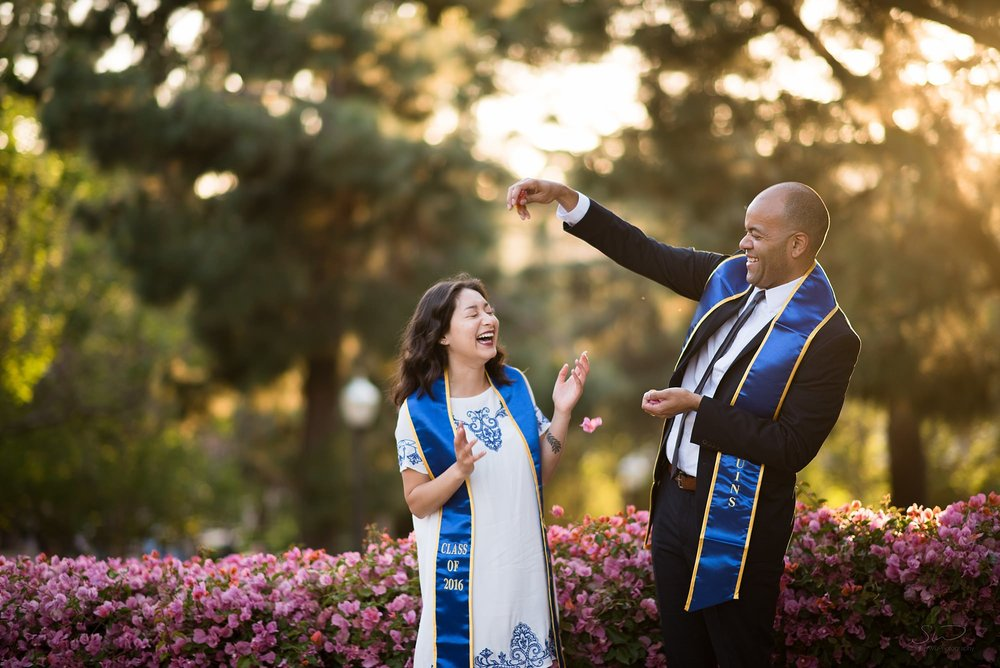 cute graduation senior portrait of two friends sprinkling flowers on each other in a green and golden sunset setting and laughing at ucla in los angeles