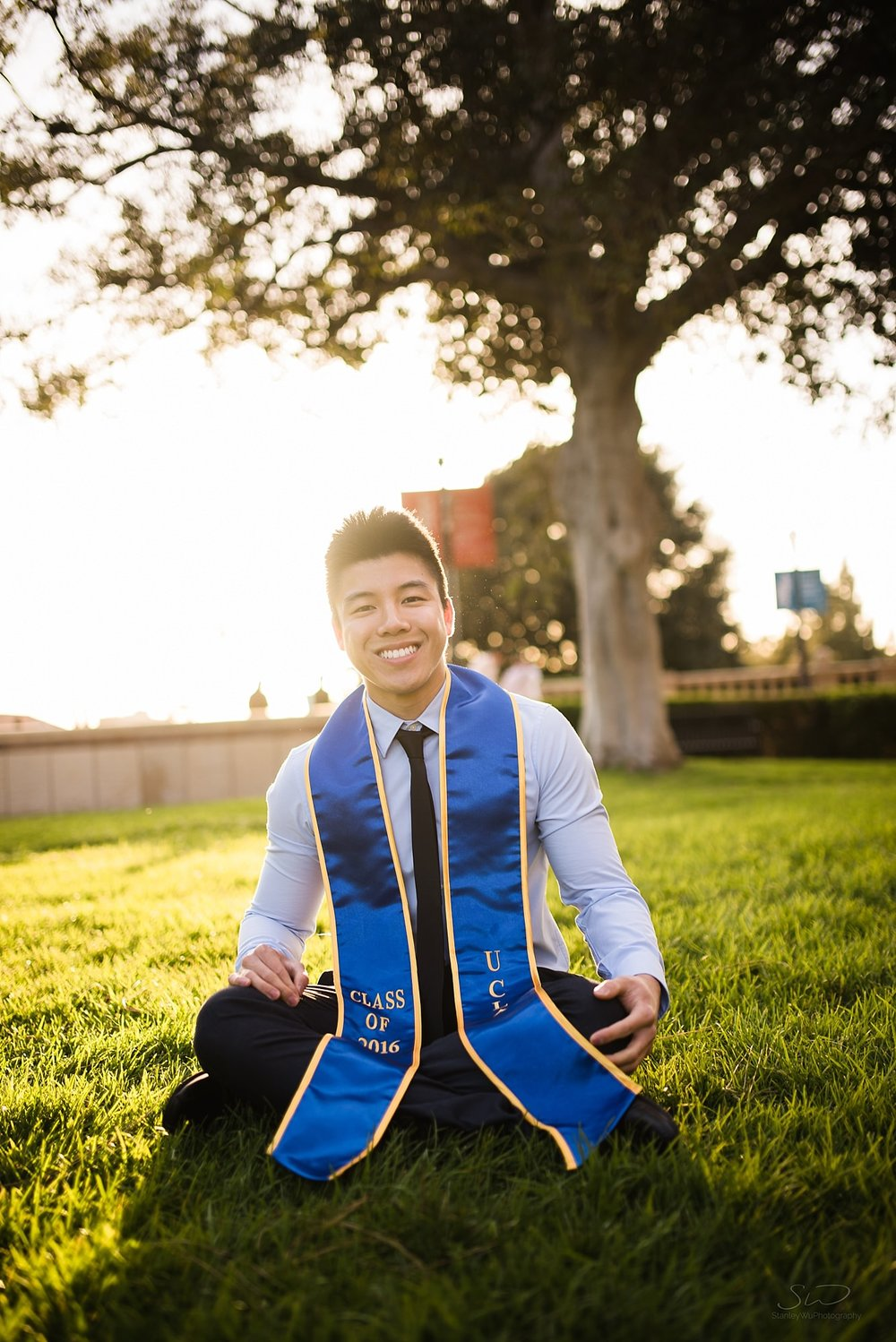 graduation senior portrait of a guy smiling sitting cross legged on grass in front of a tree at ucla in los angeles