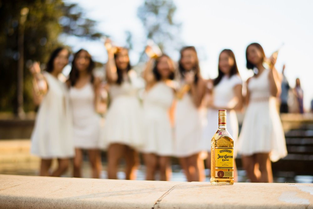 fun graduation senior portrait of a group of girls standing in a fountain blurred out with a bottle of tequila in the foreground at ucla in los angeles