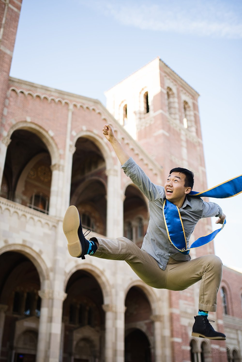 epic graduation senior portrait of a guy jumping enthusiastically in front of royce at ucla in los angeles