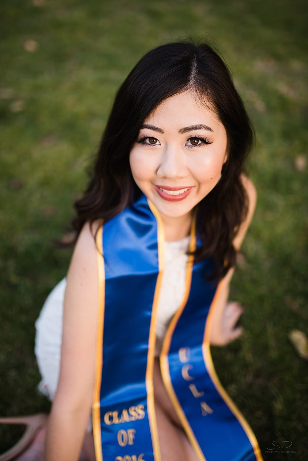 beautiful graduation senior portrait of an asian girl sitting on grass at ucla in los angeles