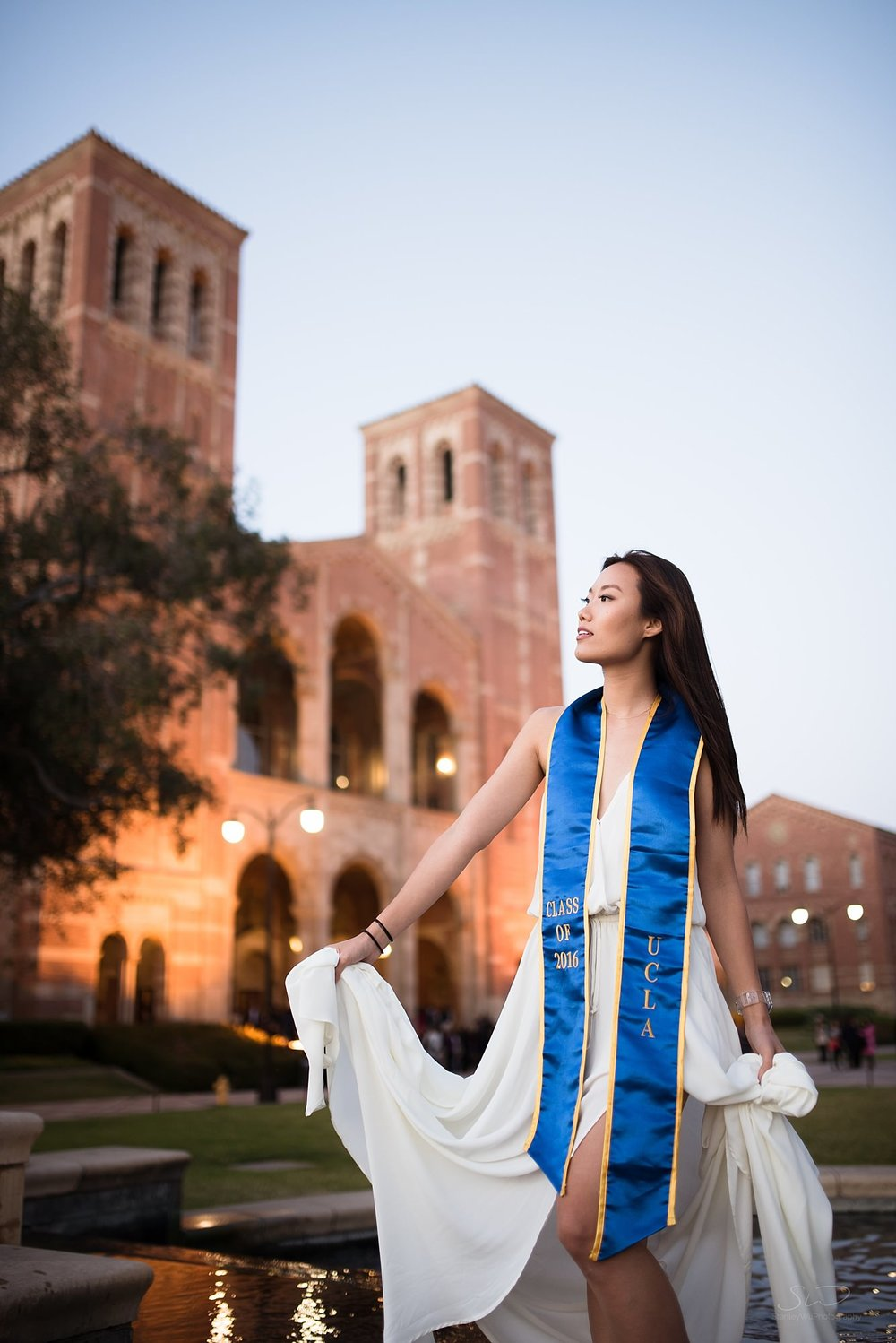 los angeles graduation senior portrait asian girl with white dress at ucla in shapiro fountain in front of royce hall