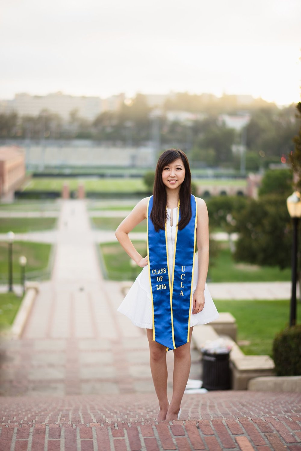 beautiful graduation senior portrait of posed girl smiling at the camera on janss steps at ucla in los angeles