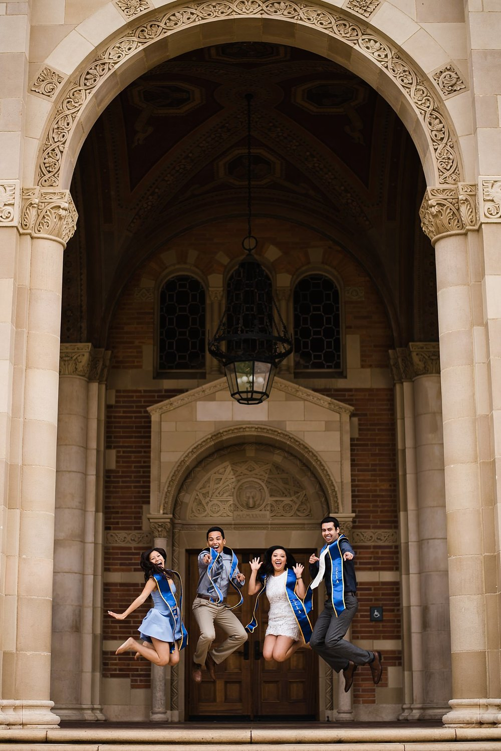 graduation senior portrait of a group jumping in unison under an arch at royce hall at ucla in los angeles