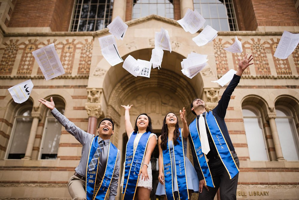 fun graduation senior portrait of a group throwing their exam papers after being done with college in front of powell library at ucla in los angeles