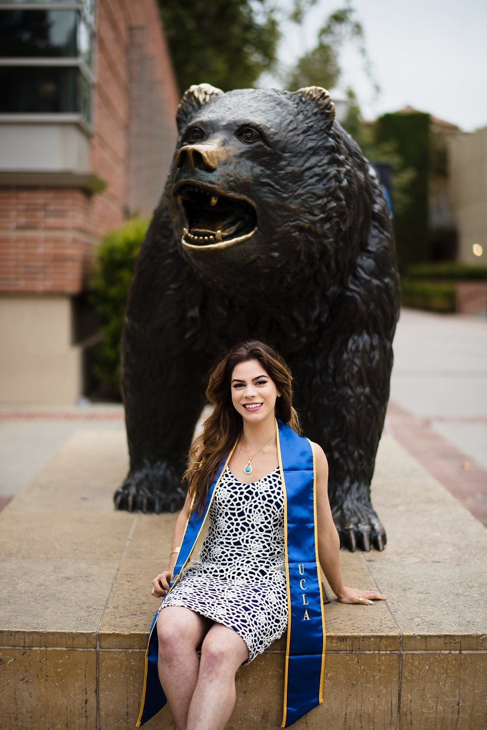 beautiful graduation senior portrait of a girl smiling in front of the bruin bear at ucla in los angeles