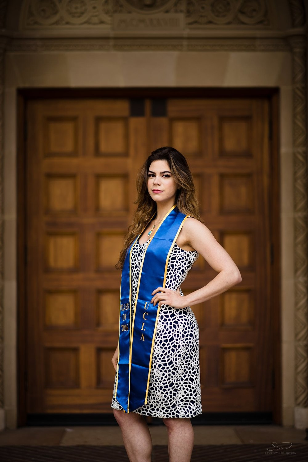 beautiful graduation senior portrait of a girl posing in front of wooden doors in royce at ucla in los angeles
