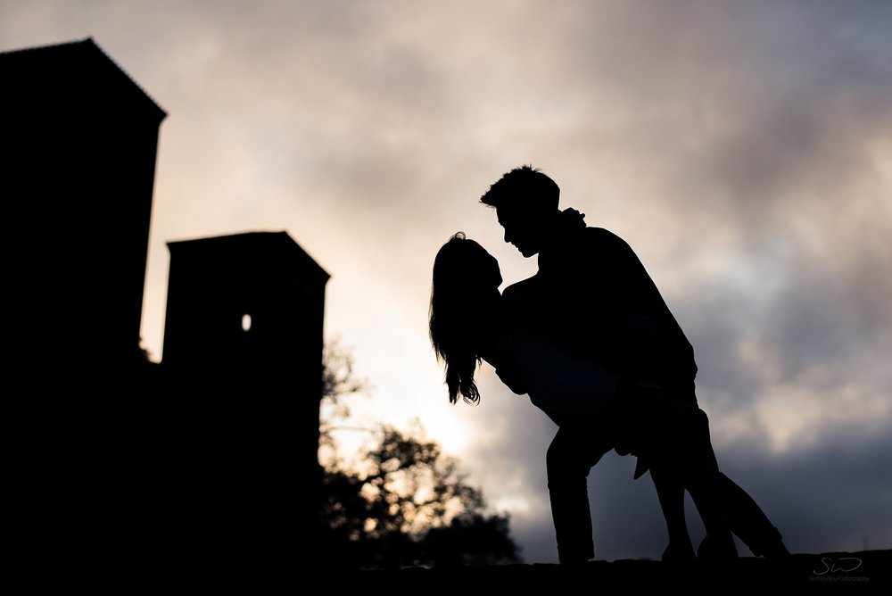 epic graduation senior silhouette portrait of a couple dipping on top of janss steps with an epic sunrise and royce hall in the background at ucla in los angeles