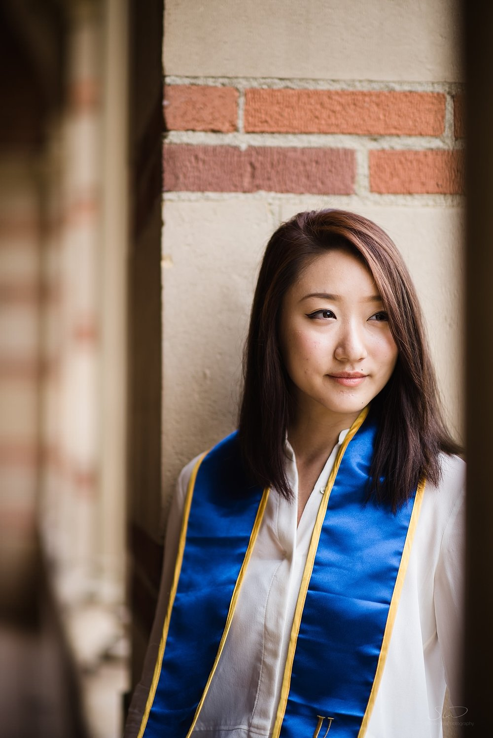beautiful graduation senior portrait of a girl looking off camera at ucla in los angeles